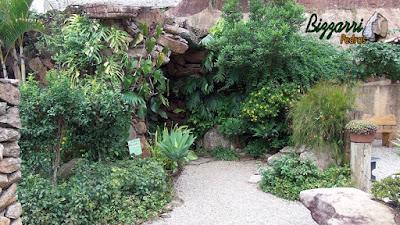 Detalhe da construção da entrada da gruta de pedra, com pedra moledo, com execução do paisagismo, com o banco de pedra e o piso de pedrisco.