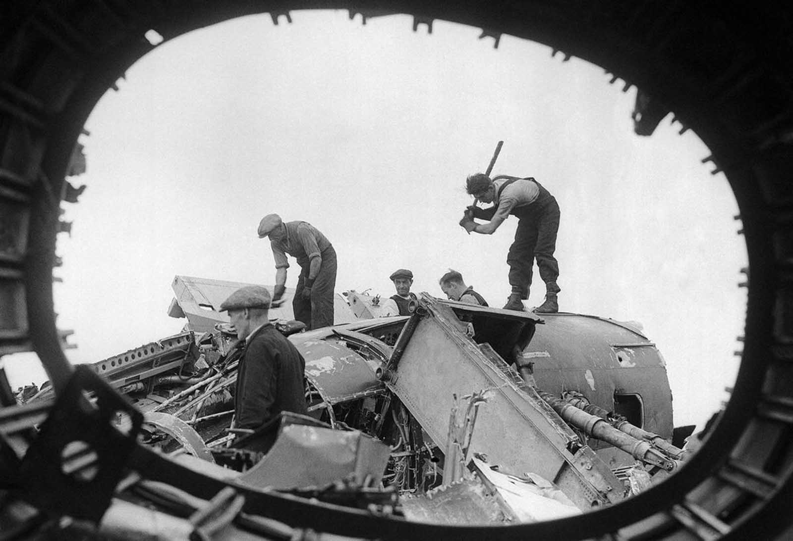 British workers in a salvage yard break up the remains of wrecked German raiders which were shot down over England, on August 26, 1940.