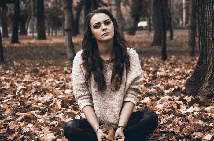 mulher sentada no ch'ao com cara de triste
