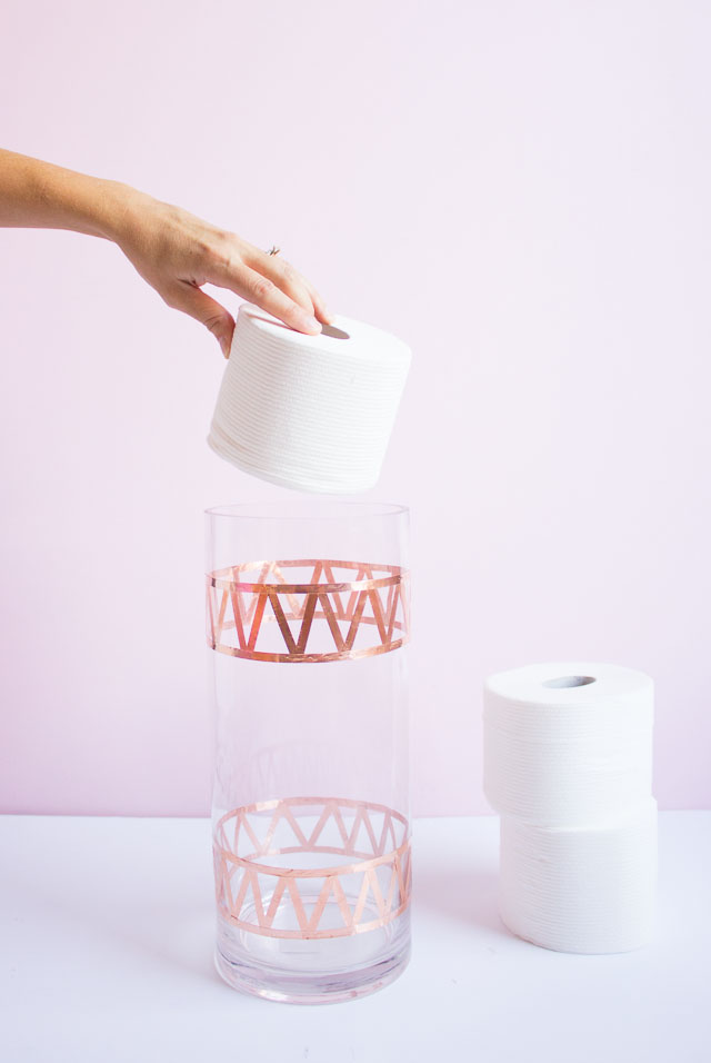 Transform an old vase into chic bath tissue storage!