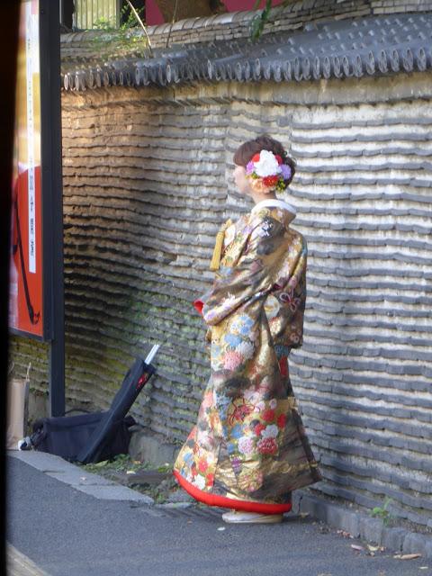 Mujer con Yukata en la entrada del templo