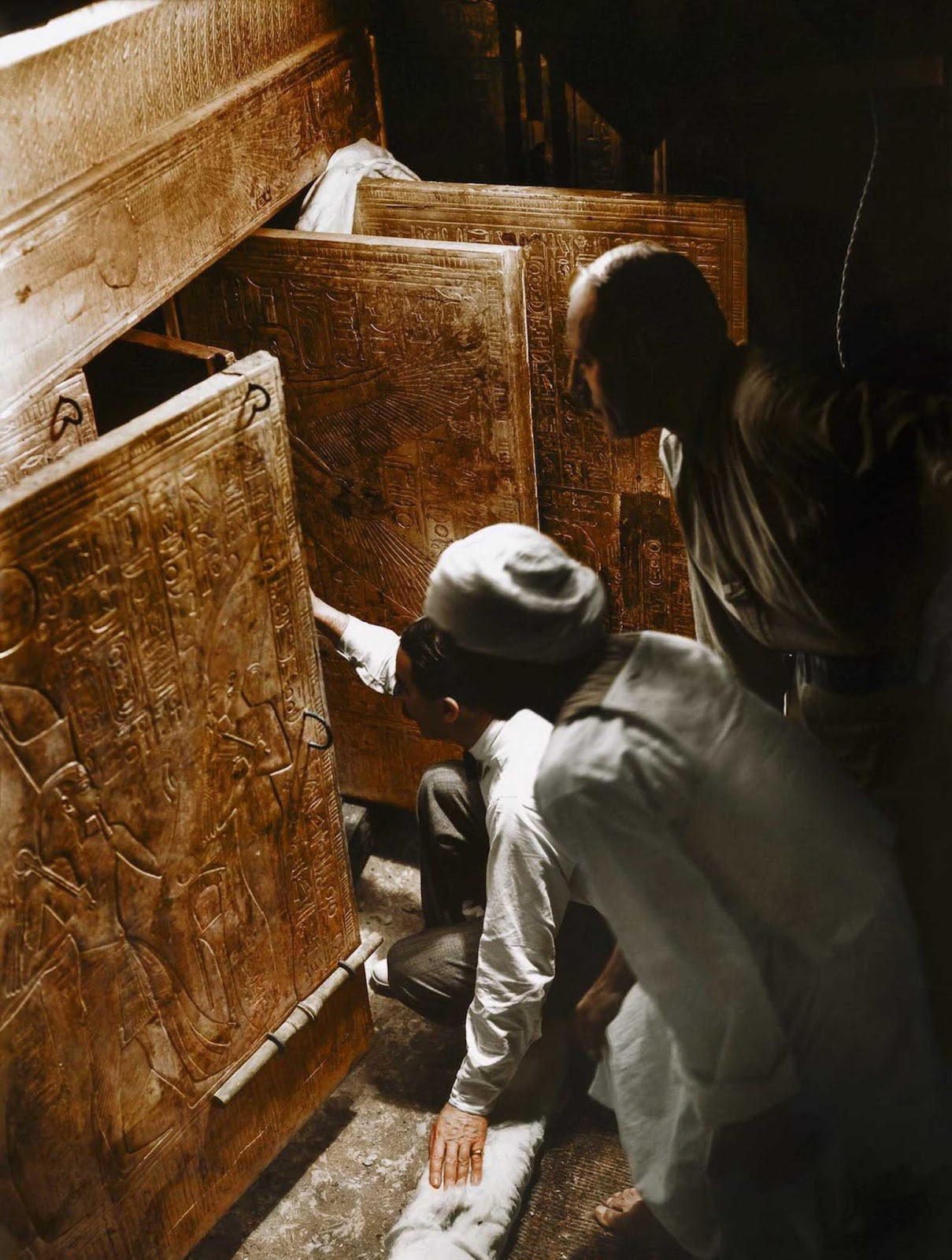 Howard Carter, Arthur Callender and an Egyptian worker open the doors of the innermost shrine and get their first look at Tutankhamun's sarcophagus.