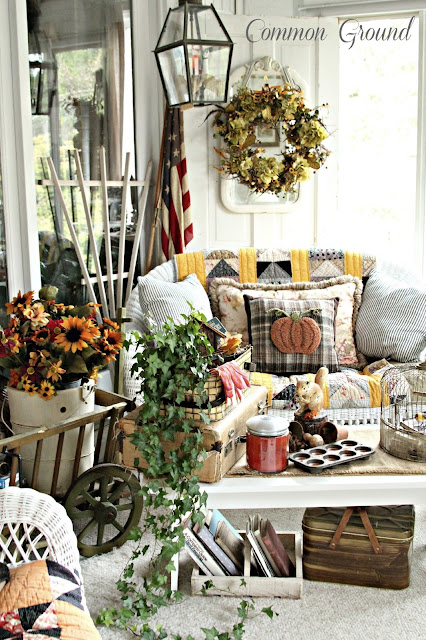 This decorative front porch with pumpkin and flower decor all around is great for autumn.