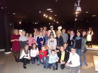 Na fotografii 21 osób z Pomorskiego TPG i Wejherowskiego PZG wraz z kuratorką wystawy i pracownikami Muzeum Miasta Gdyni. W tle manekiny w filmowych kostiumach.
