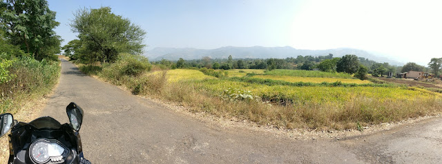 panorama shot of the road to pabe ghat with ride fields surrounding