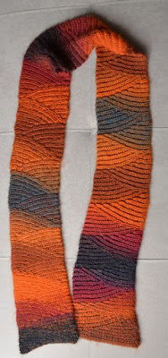Vesuvius slip stitch scarf graduating colours of charcoal, deep pink reds, oranges, browns.