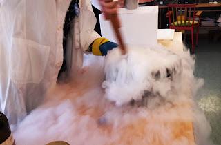 A Dra. Isabel vestida de bata branca e com luvas mexe o interior de um alguidar de onde sai fumo branco que se espalha pela secretária: a cozinhar o cometa
