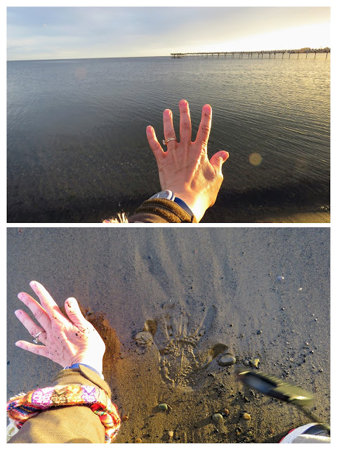 Pressing a hand in the sand on the shores of the Strait of Magellan in Punta Arenas