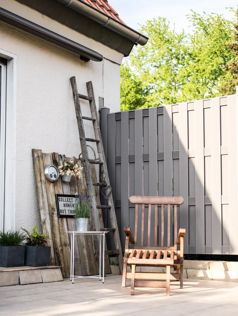 www.fim.works | Lifestyle-Blog | Terrasse mit Deckchair, Terrassendeko, WPC-Sichtschutz in Grau, altes Holz als Deko auf der Terrasse