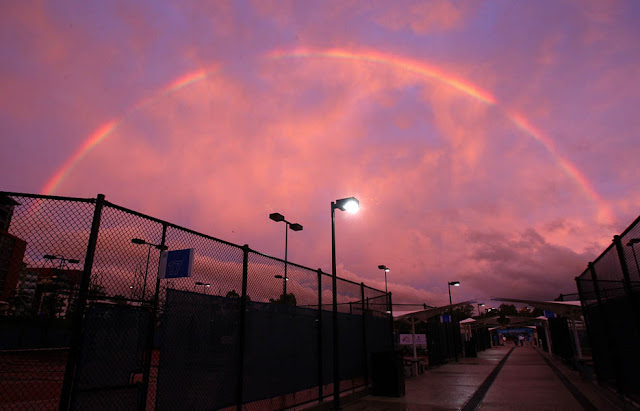 A rainbow is seen as the sun sets at the Queensland Tennis Centre in Brisbane, Australia.