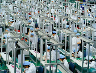 Bird Mobile, Ningbo, Zhejiang Province, 2005, The largest mobile-phone manufacturer in China when this photo was shot, Bird Mobile has since been overtaken. Here, workers complete a manual-assembly portion of the phone-production process. (Photo Credit: Ed Burtynsky) Click to Enlarge.