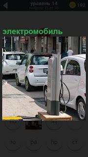 Вдоль дороги стоят электромобили и происходит зарядка аккумулятора
