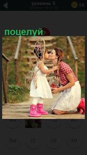 на мосту мама целует свою дочку