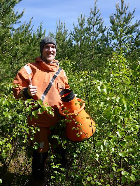 Mies seisoo pelastautumispuvussa keskellä metsää vesikiikarin kanssa