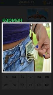 открытый карман джинсов, в котором находятся деньги