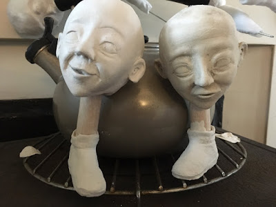 two sculpted heads drying on a stove, each resting on a sculpted lower leg. By Artist Corina Duyn