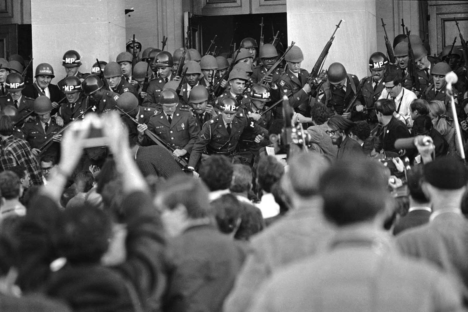 Military police, reinforced by Army troops, throw back anti-war demonstrators as they tried to storm a mall entrance doorway at the Pentagon in Washington, D.C., on October 21, 1967.