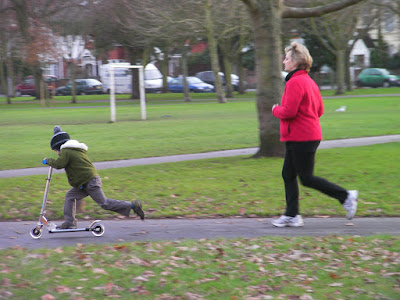 boy on christmas present scooter and jogging mother