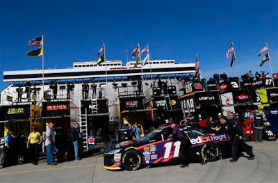 Crew members push the #11 FedEx Freight Toyota,  of Denny Hamlin through the garage area during practice.