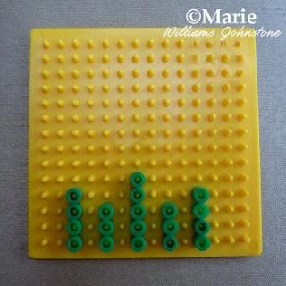 Starting pattern of green beads on yellow pegboard