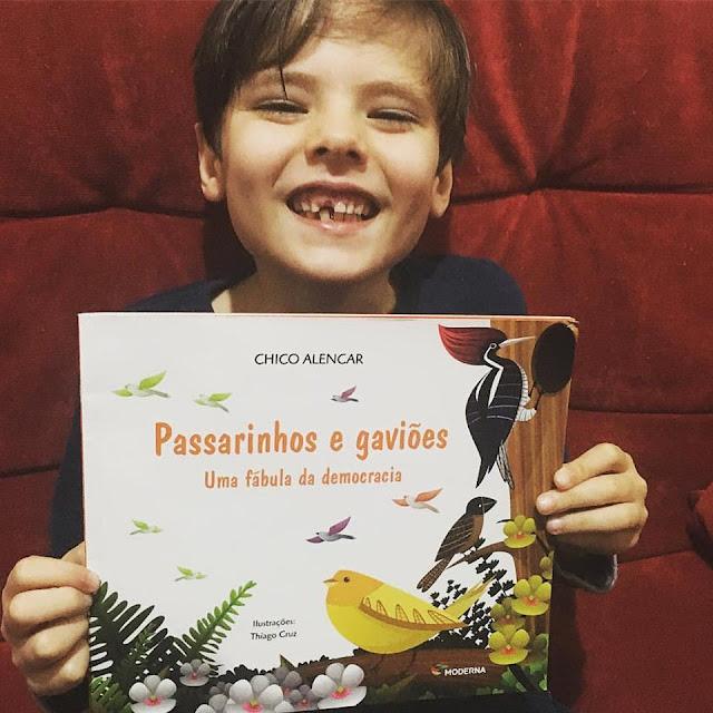 """Foto do meu filho segurando nosso exemplar do livro ilustrado """"Passarinhos e Gaviões"""", escrito pelo deputado Chico Alencar."""
