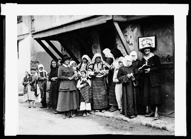 Christians and Mohammedans alike call on the A.R.C. in Southern Serbia for aid. These women have lined up outside a Red Cross office in Monastir with applications and recommendations for medical relief and food. Miss Saxton and Miss Carolyn Mountain are the two Red Cross workers in charge of the relief lists. The first two women with their faces veiled are of Turkish descent and Mohammadan faith. The house in the background is a typical Turkish residence of this country. The overhanging balcony is especially built for the harem, in order that the women might look up and down the street from little grilled windows without being seen