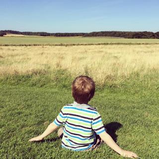 Autistic boy sitting on grass