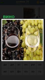 стоят два бокала вина и лежит виноград из которого оно сделано
