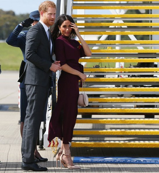 Meghan Markle wore Hugo Boss Eodora dark pink midi dress, and Aquazzura Casablanca style pumps she carried the Cuyana handbag