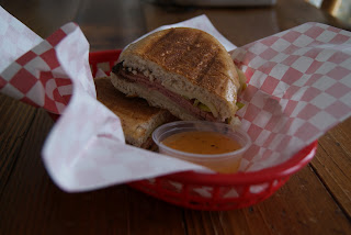 One sliced Italian beef on sandwich, served with a side of Italian dressing in a red basket.