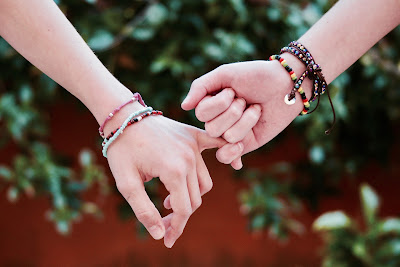 two girls' hands with friendship bracelets