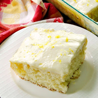 Sunshine Lemon Poke Cake in a glass dish on a wooden table with a yellow and red plaid table runner.