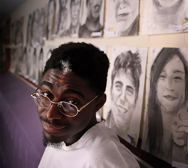 Photo of Philip Sossou behind some of his charcoal portrait sketches