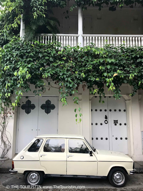 A classic white car in front of the ornate white doors of a facade covered in plant leaves.