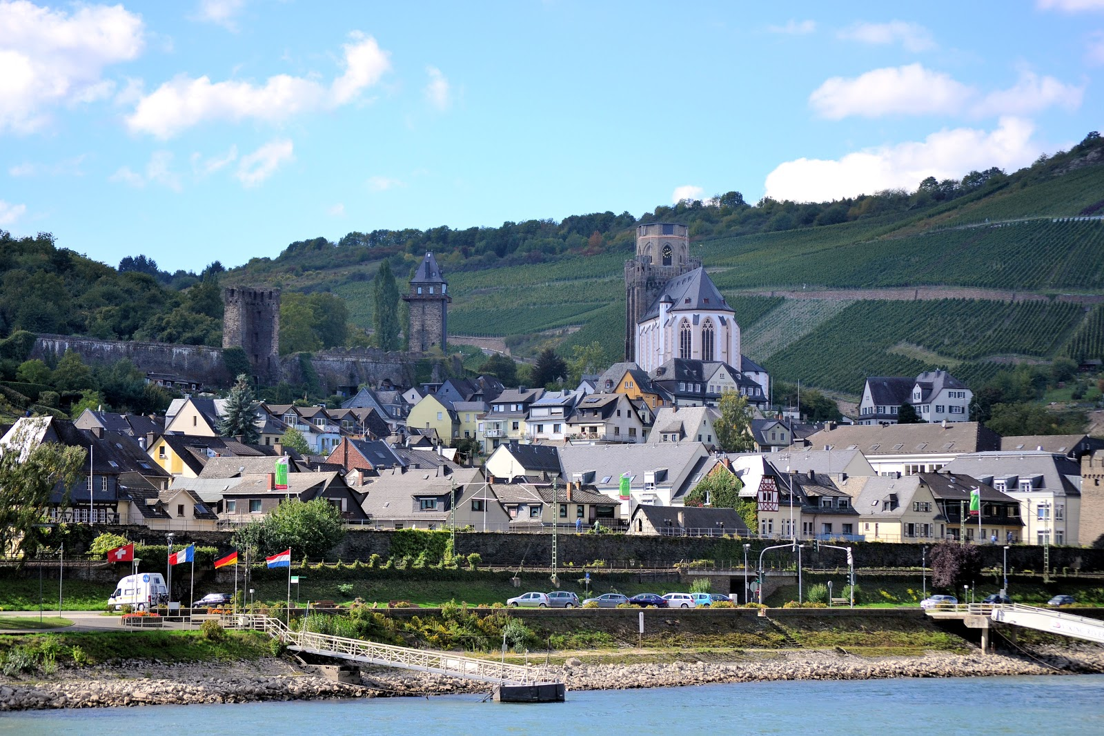 Oberwesel, Germany, lies on the banks of the Rhine River. St. Martin's Church rises alongside the vineyards in the background. Two of the original 21 watch towers stand to the left.