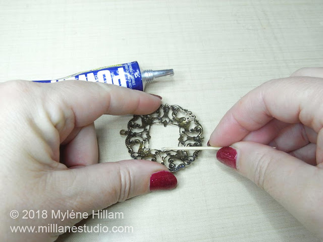 Using a toothpick to apply the adhesive to the fine detail of the filigree
