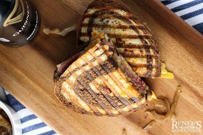 Corned Beef Panini with Caramelized Guinness Onions cut in half on a board overhead view with Guinness can to the side
