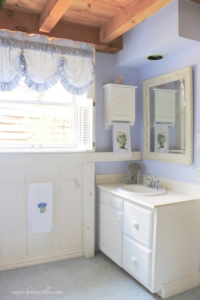 small vanity painted white with a new white wood carved mirror