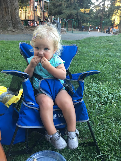 toddler sitting in a portable high chair/camping chair at a soccer game