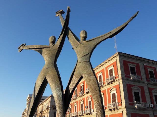 Statua di due marinai con braccia alzate