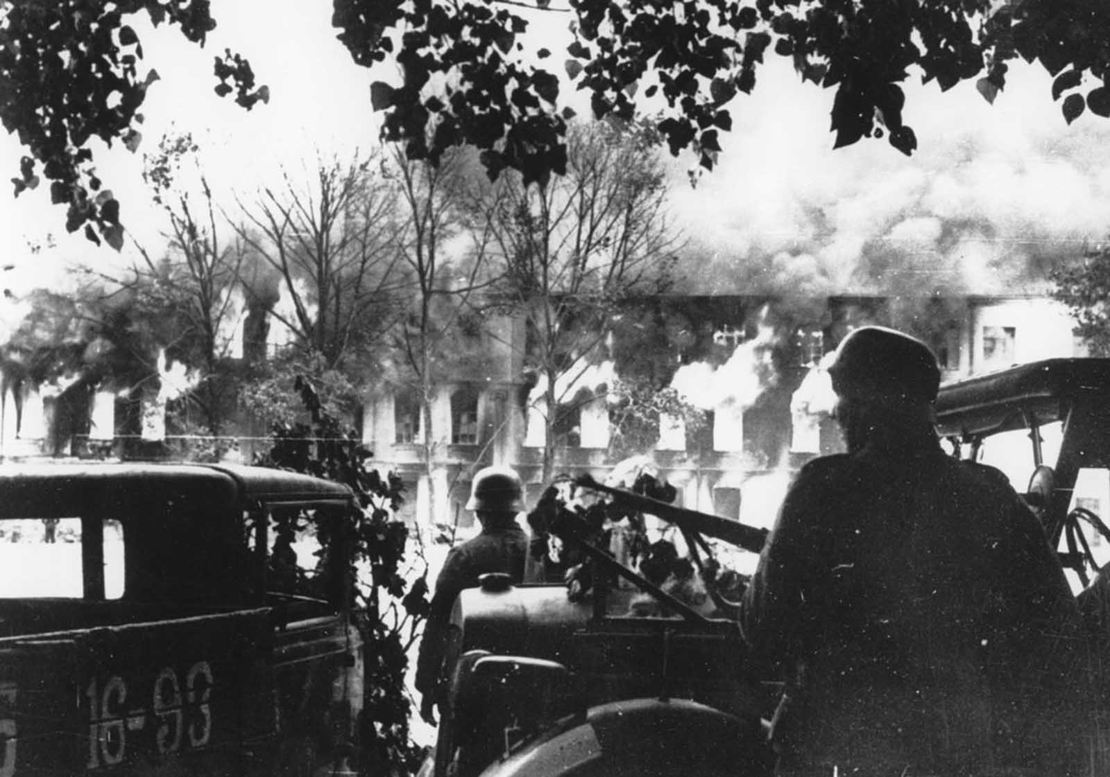 Flames shoot high from burning buildings in the background as German troops enter the city of Smolensk, in the central Soviet Union, during their offensive drive onto the capital Moscow, in August of 1941.