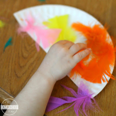 cut a paper plate in half and glue feathers on