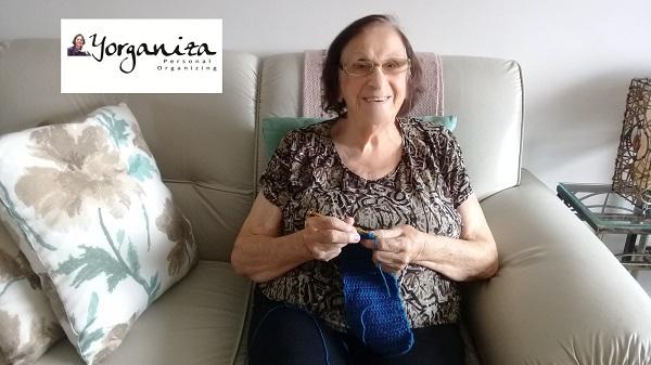 Senhora idosa fazendo saquinhos de lã no crochê