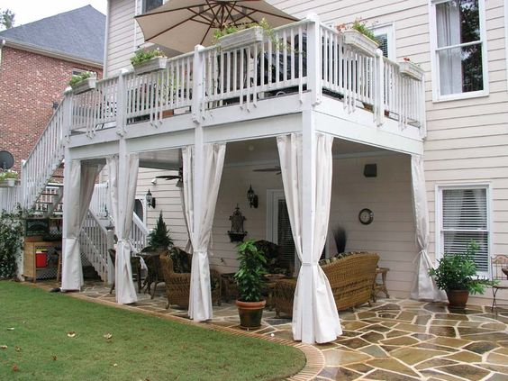 white second story deck with underneath family area and back staircase