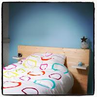 lit et tête de lit devant mur bleu