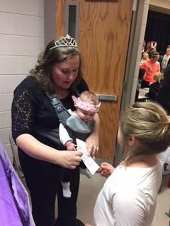 Lady in black in princess crown holding a baby handing a paper to a young girl