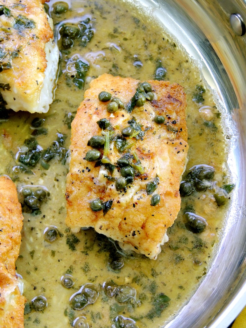 Close up of Pan-Roasted Cod with Lemon White Wine Sauce in a silver skillet.