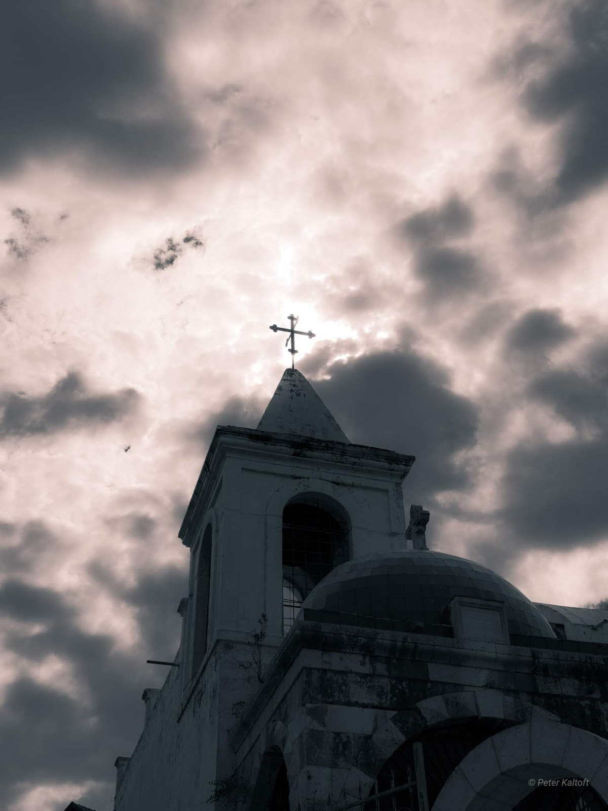 The cross on top of the Coptic church in Jaffa surrounded by the glow of the sun behind clouds.