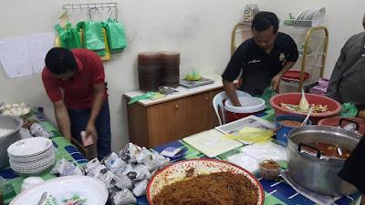 dua orang anak Mak Cik Jenab sedang sibuk menyediakan dan membungkus nasi minyak