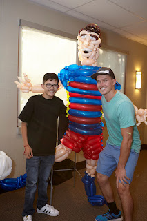The Utah Balloon Artist with a young boy with cancer next to a life size balloon sculpture of Lionel Messi